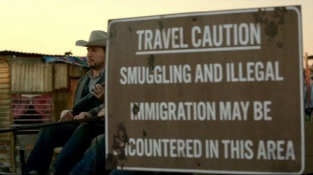 Revolution S2x10 - Miles, Rachel and Bass pass by an illegal immigration sign warning as they volunteer to pick tomatos